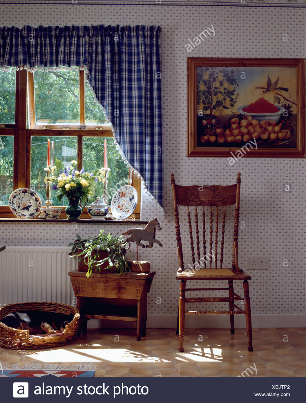 Picture On Wall Beside Window With Blue Checked Curtains In Dining Room  With Wallpaper And Antique Chair And Stool