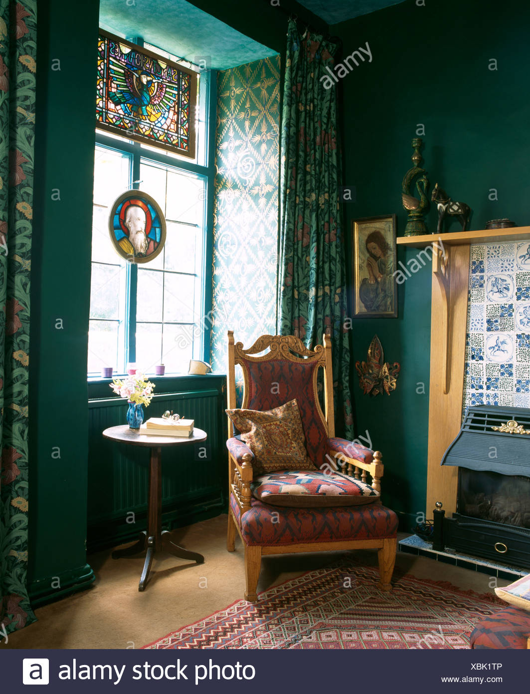 Edwardian Armchair Beside Fireplace With Electric Fire In Dark Green Living  Room With Stained Glass Panel In Window
