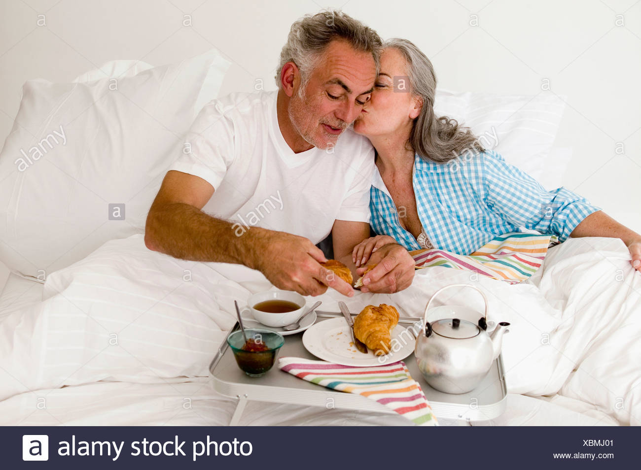 Women kissing on bed