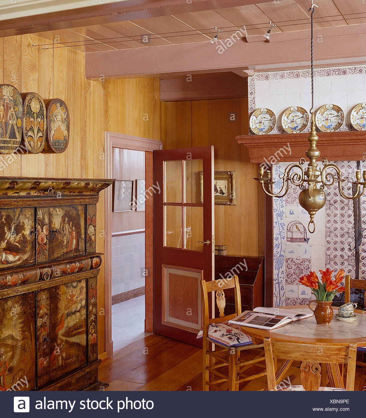 Brass Chandelier Above Circular Pine Table And Chairs In Country Dining Room  With Antique Painted Cupboard And Half Glazed Door