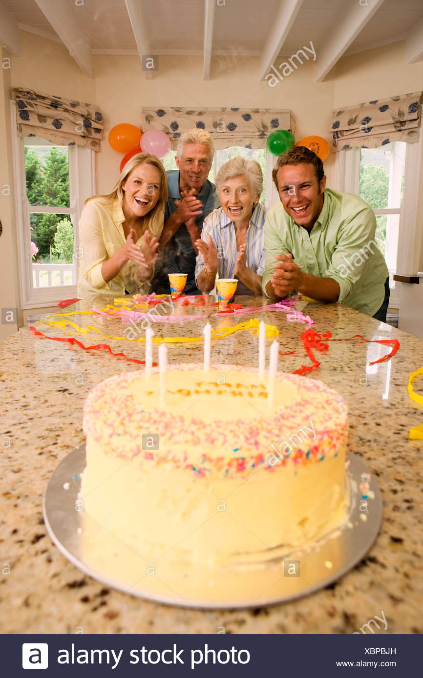 Parents And Grandparents Celebrating Birthday At Home Smiling Portrait Cake On Table In Foreground