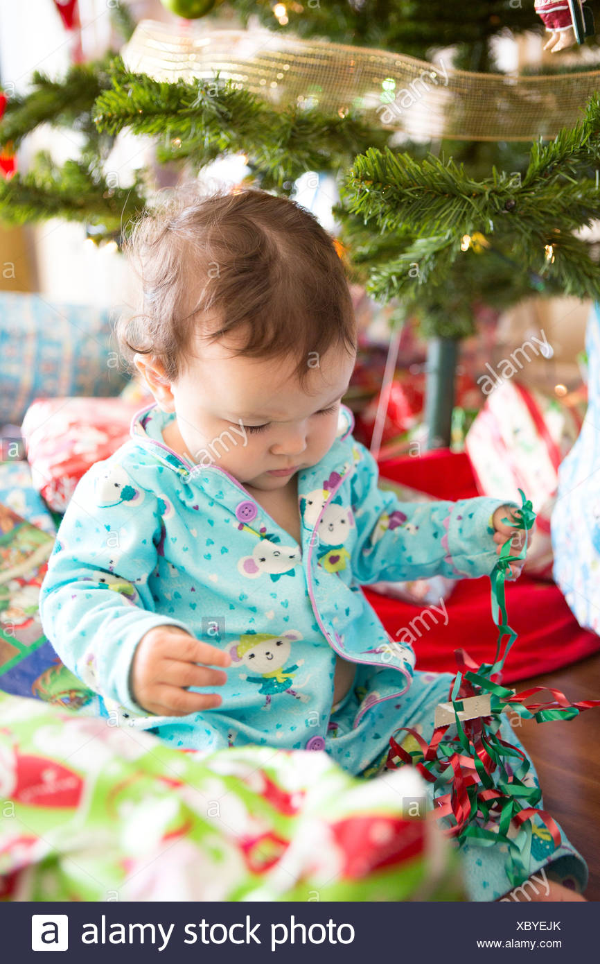 baby girl opening christmas presents on her first christmas