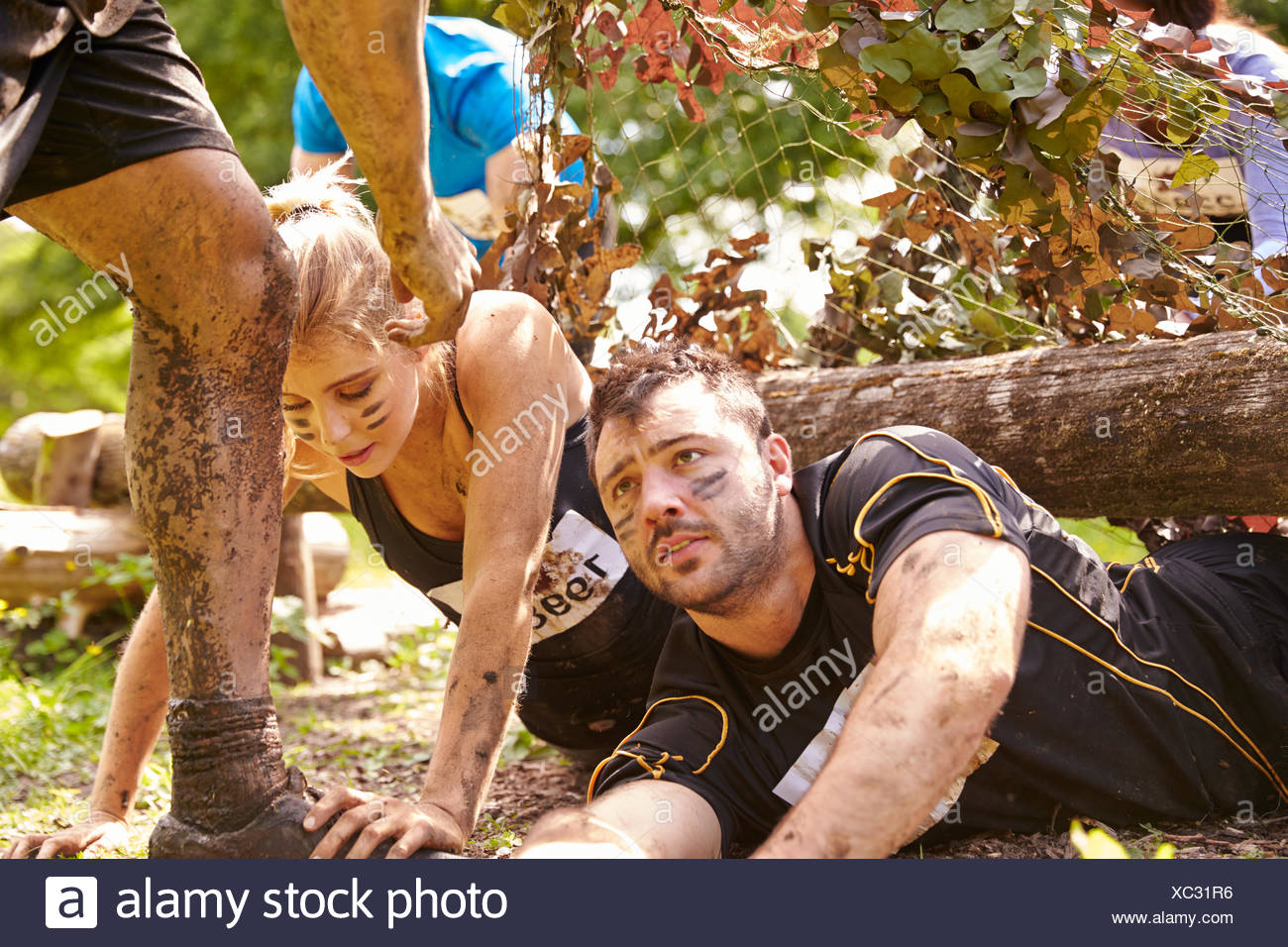 assault course competitor helping others crawl under nets stock