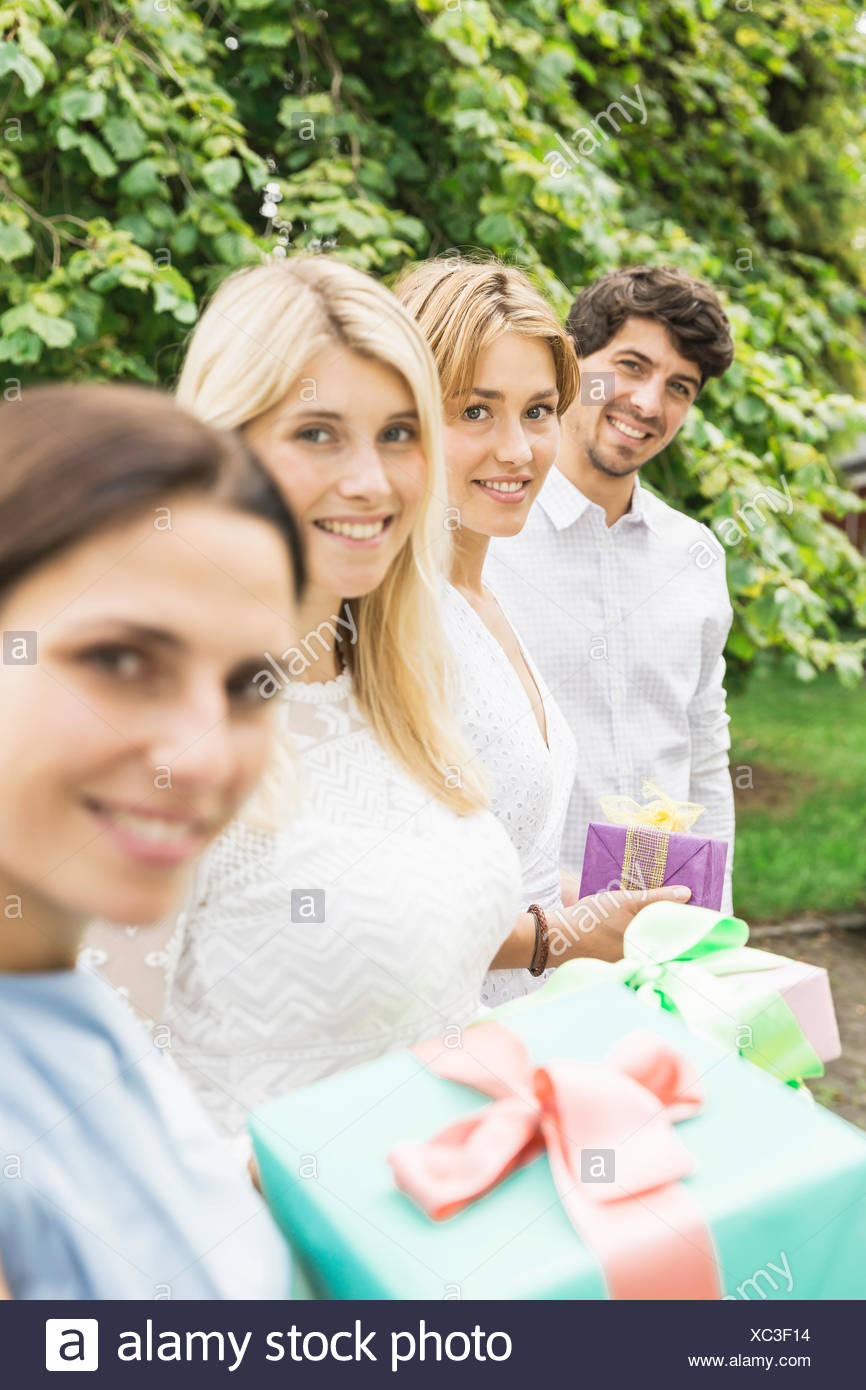 Portrait Of Young Man And Three Women Holding Birthday Gifts In Garden