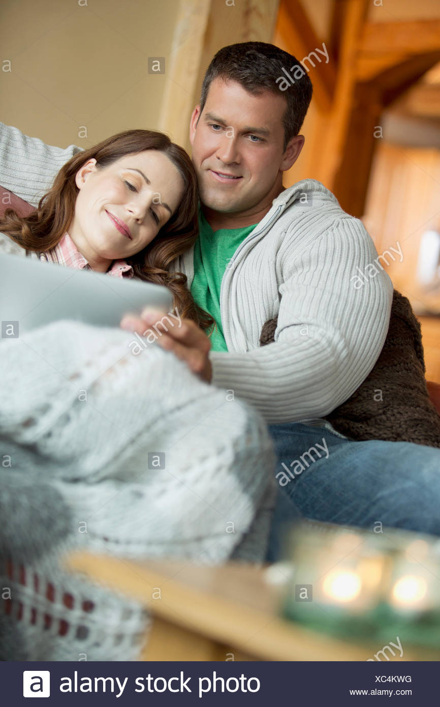 Mid Adult Couple Cuddling On Sofa With Pc Tablet