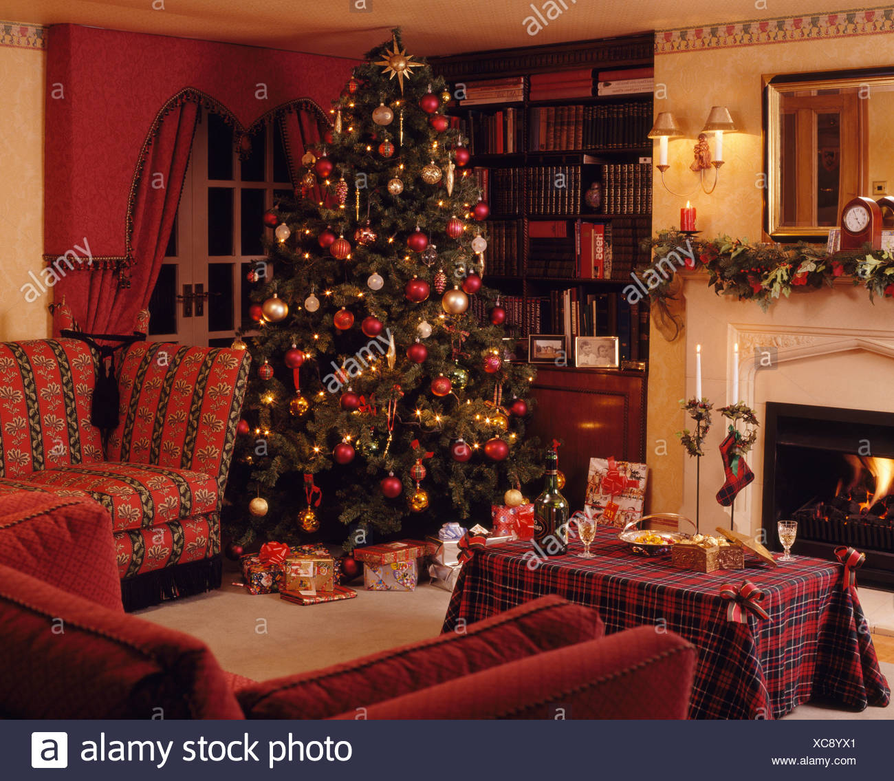 Wrapped Gifts Below Christmas Tree In Corner Of Traditional Country Living Room With Red Tartan Cloth On Coffee Table