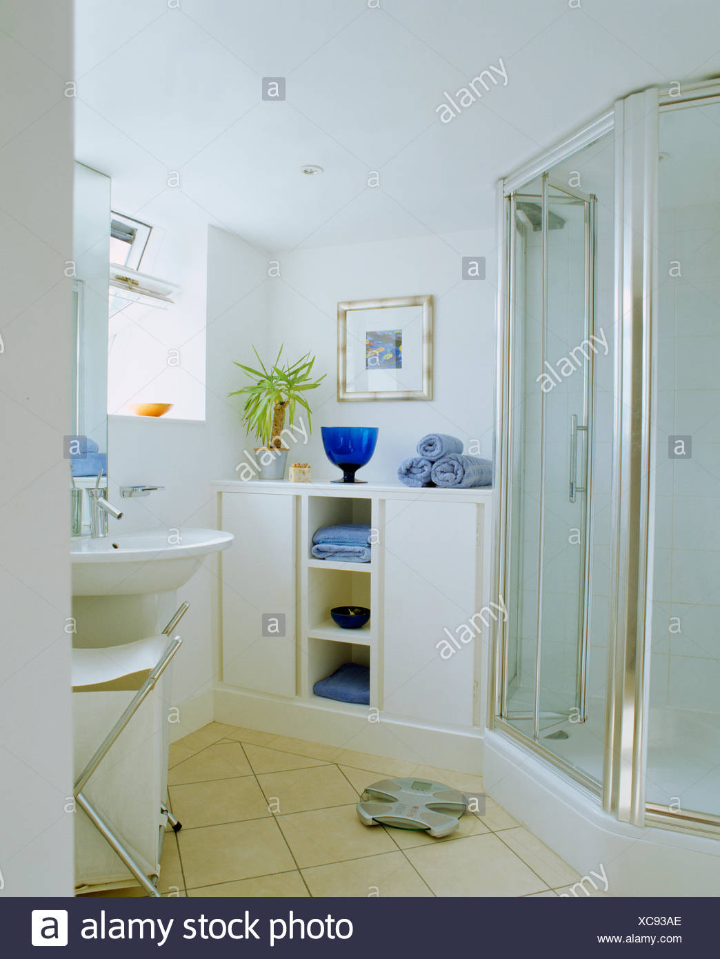 Large Blue Glass Vase And Pale Blue Towels On Shelf Unit In Modern White  Bathroom With Glass Shower Doors