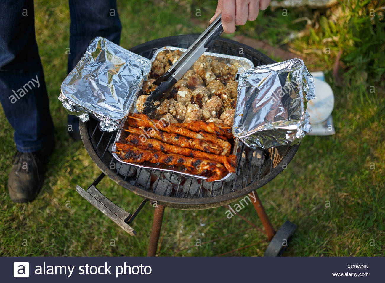 emden, germany, on a charcoal grill in a foil dish are meat and