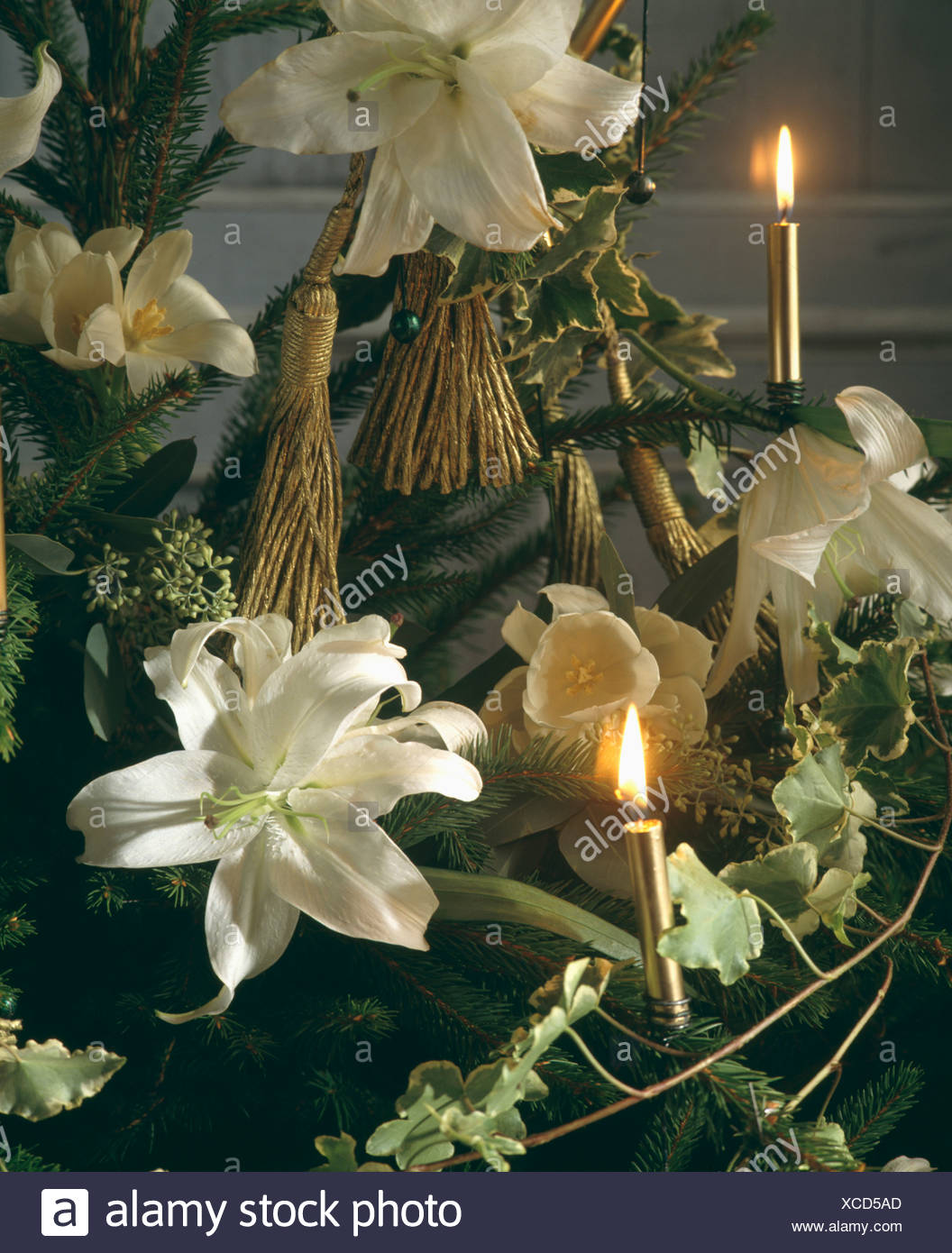 close up of christmas tree with small lighted candles and fresh white lily decorations - Small Lighted Christmas Tree