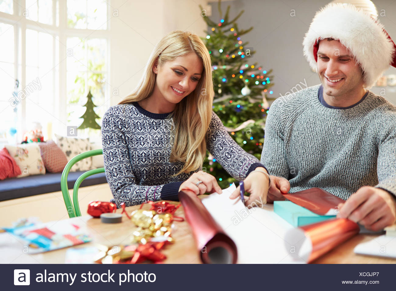 Couple Wrapping Christmas Gifts At Home Stock Photo: 283107727 - Alamy