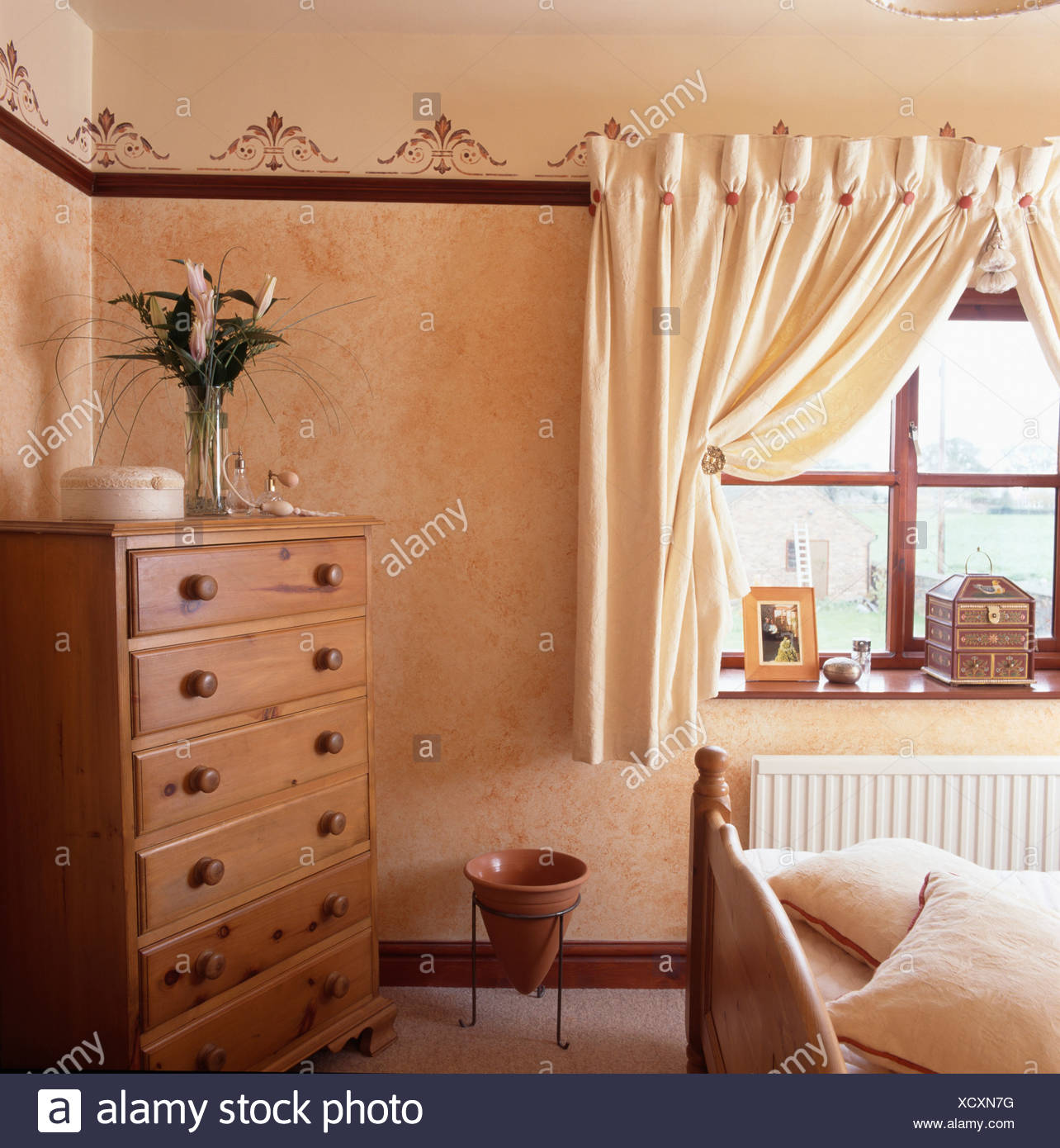 Chest-of-drawers in corner of small bedroom with cream curtains at ...