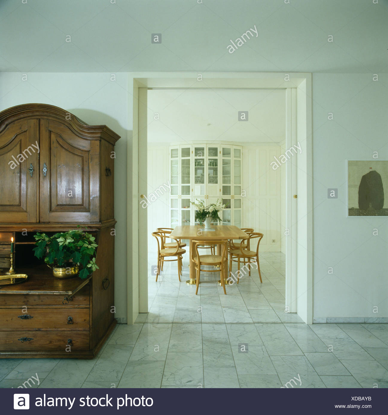 Antique cupboard in modern white hall with marble tiled floor and with view  of dining room through open double doors - Antique Cupboard In Modern White Hall With Marble Tiled Floor And