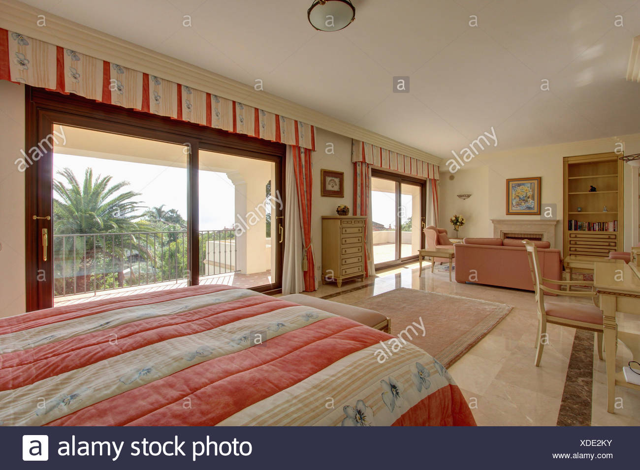 Pink Striped Quilt On Bed In Spanish Studio Apartment Bedroom With