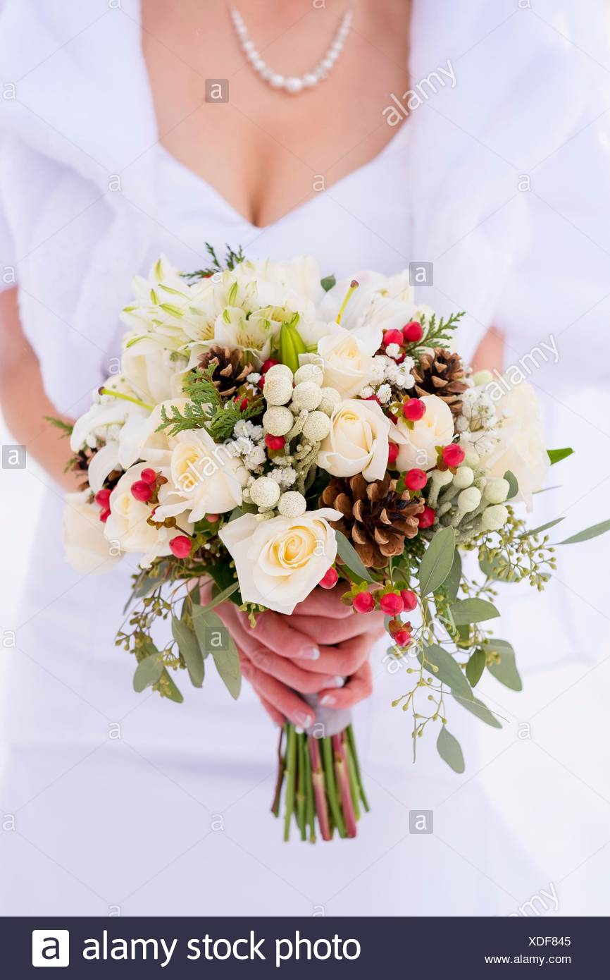 Bride holding a beautiful winter bouquet of flowers featuring white bride holding a beautiful winter bouquet of flowers featuring white roses and holly berries in the snow izmirmasajfo