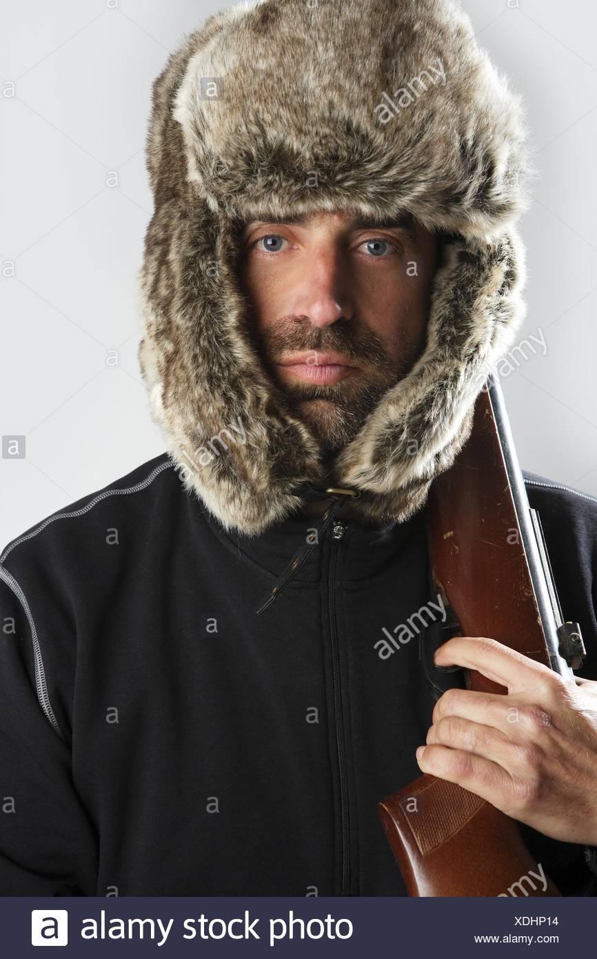 a014fc1db9c hunter winter fur hat man portrait holding gun Stock Photo ...