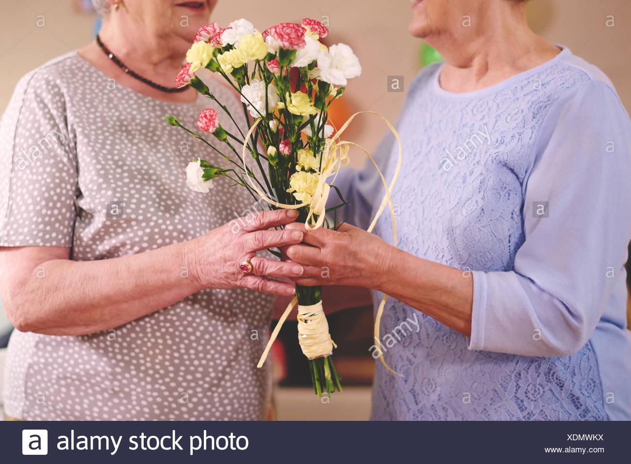 Senior Woman Giving Flowers To Friend At Birthday Party Stock Photo