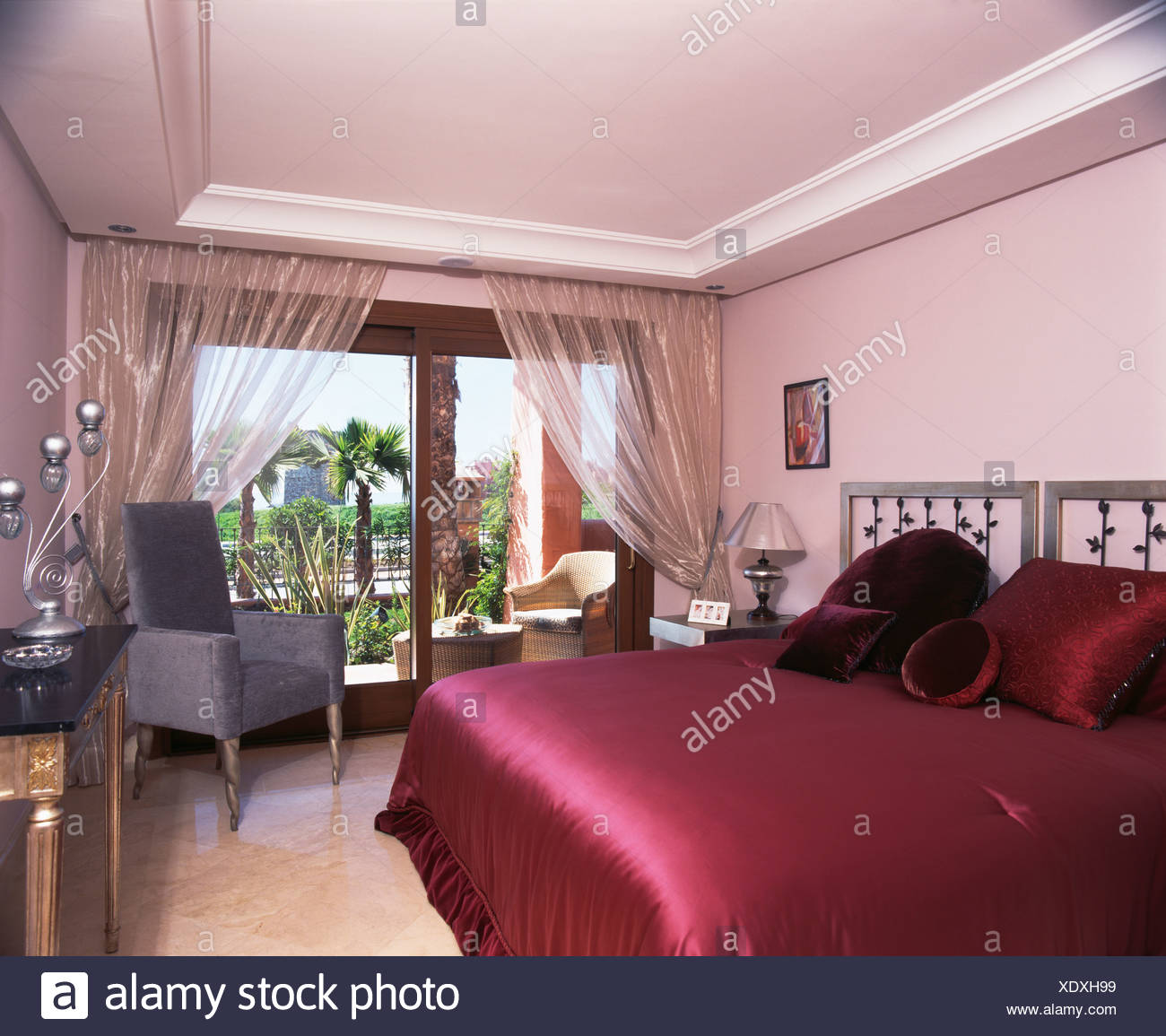 Ordinaire Red Satin Bed Cover On Bed In Modern Bedroom With Metallic Voile Curtains  On Patio Doors To Balcony