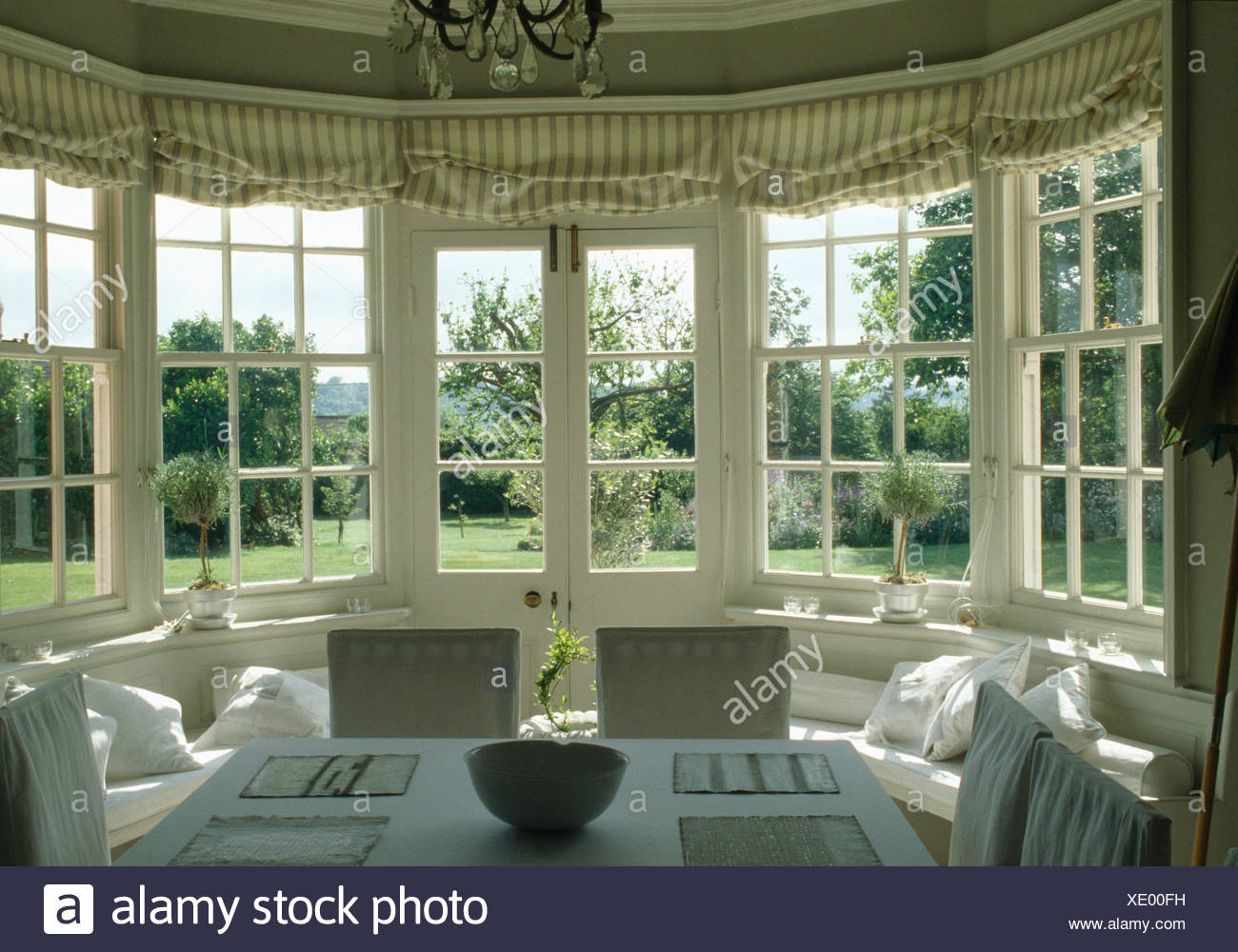 Striped Blinds On French Windows In Country Dining Room With View Of The  Garden
