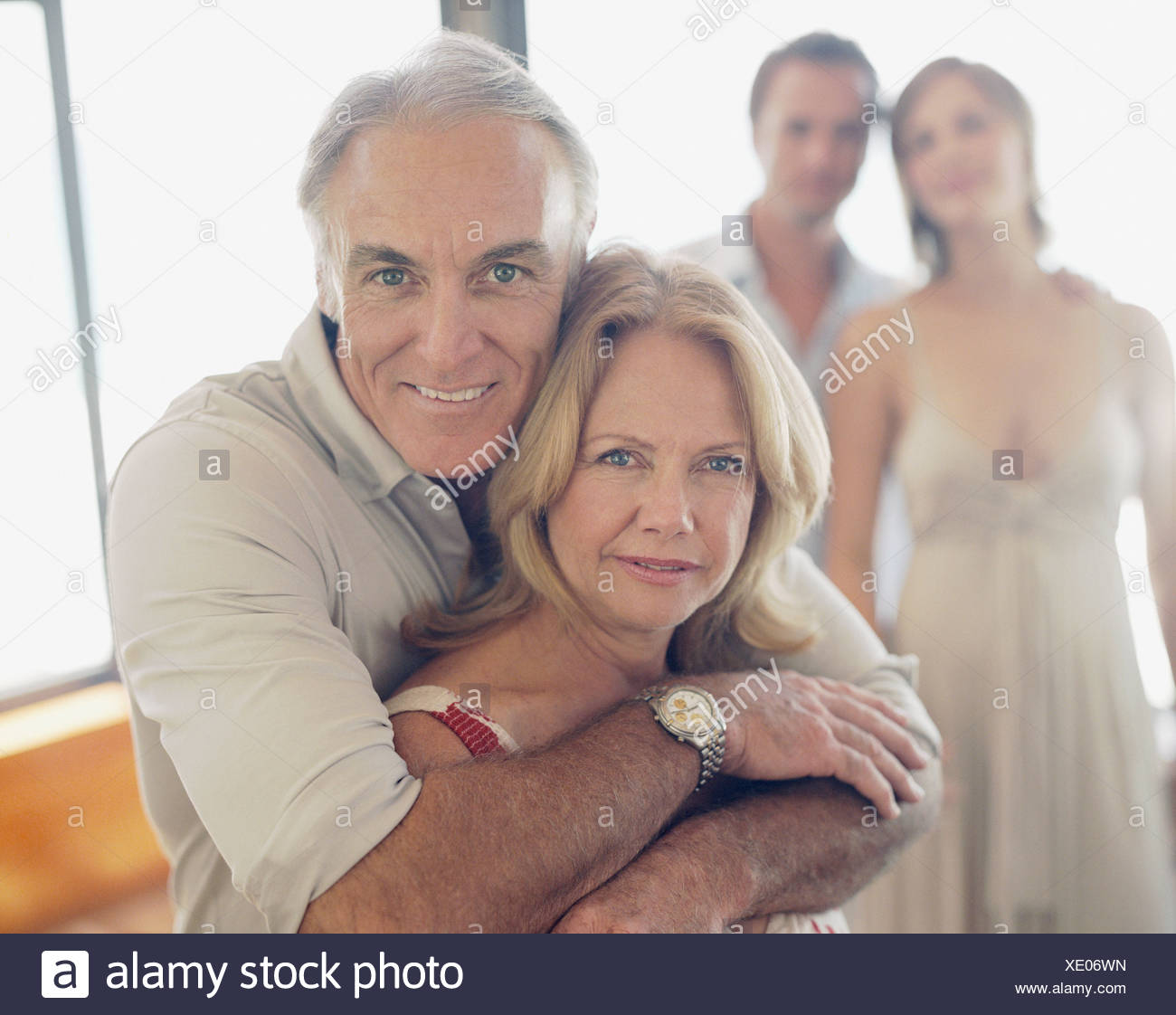 Couple Mature mature couple with younger couple in background stock photo