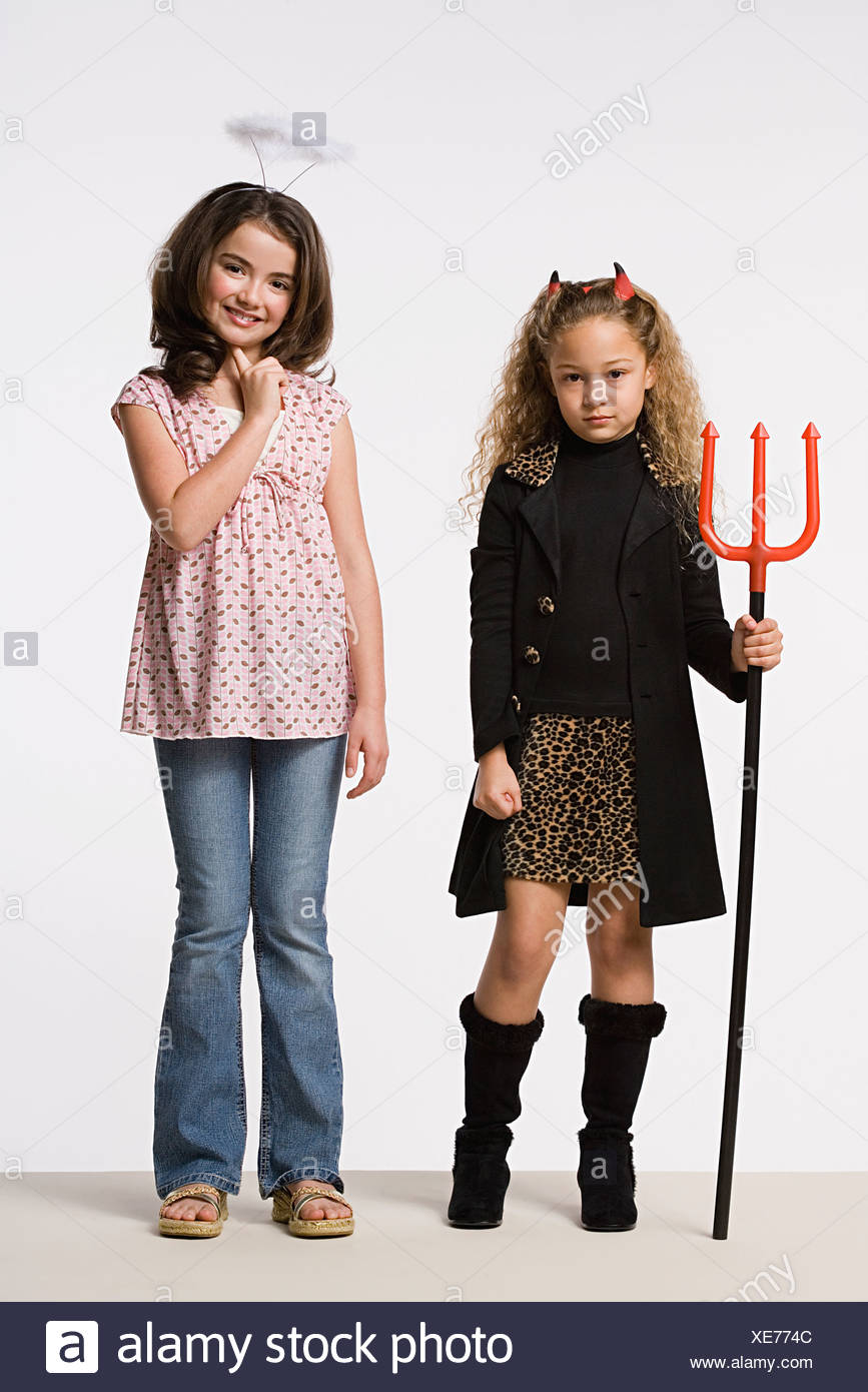 studio portrait of two girls 8 9 wearing halloween costumes with trident and halo