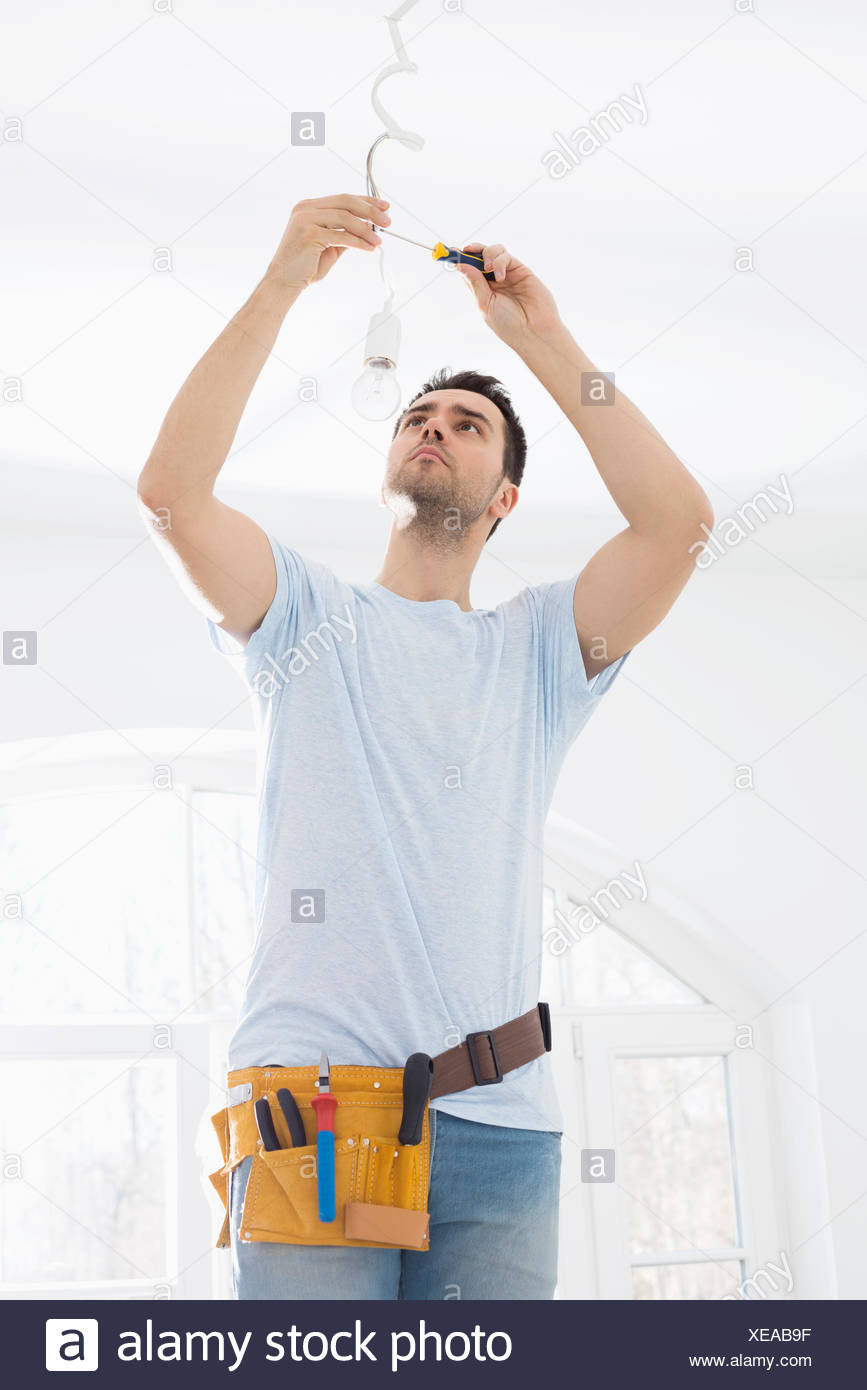 Mid Adult Man Fixing Light Bulb Wiring In New House Stock Photo