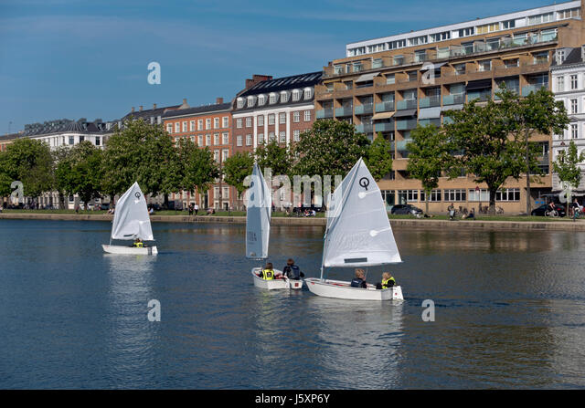 Junior sailors in optimist dinghies on the Peblinge Lake in central Copenhagen on a sunny afternoon late spring - Stock Image