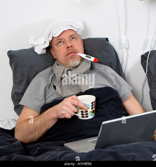 man laying in bed sick with thermometer in mouth stock image