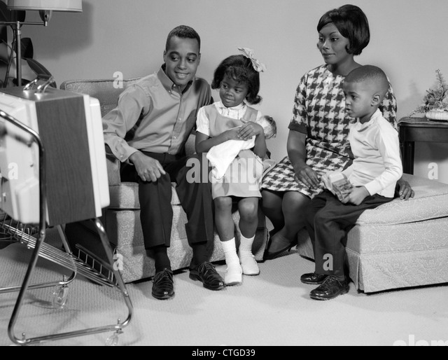black family watching tv. 1960s black family watching portable television - stock image black family watching tv