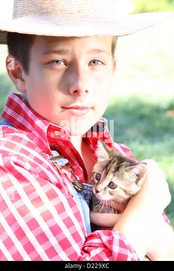 A farmer boy holding a small kitten Stock Photo - a-farmer-boy-holding-a-small-kitten-d229xc