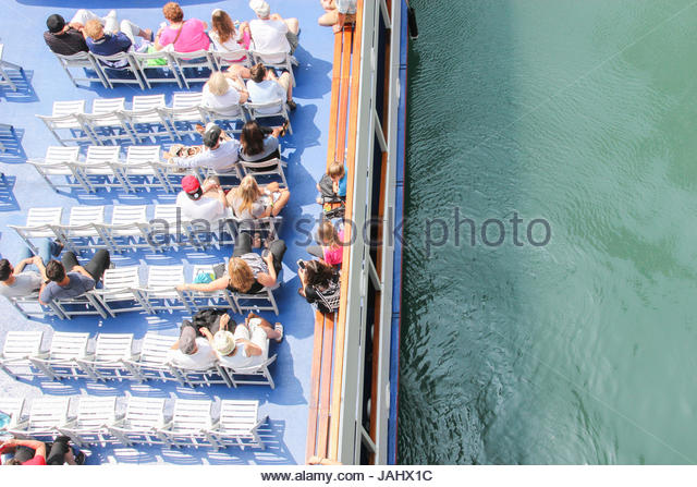 Overhead view of sightseers on a boat on the Chicago River, turned green for St. Patrick's Day. - Stock Image