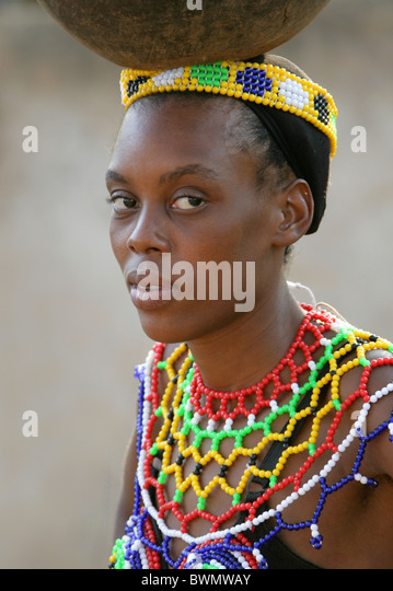 Zulu girls wearing traditional beaded dress and carrying pots on their