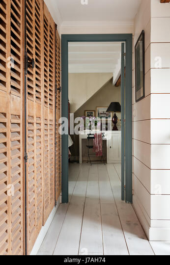 Louvered wooden storage cupboards provide generous space - Stock Image