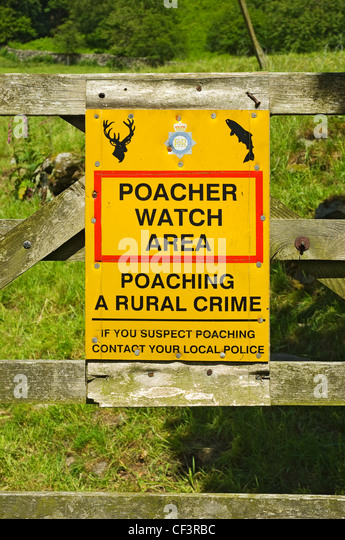 A warning sign to potential poachers attached to wooden gate. - Stock Image