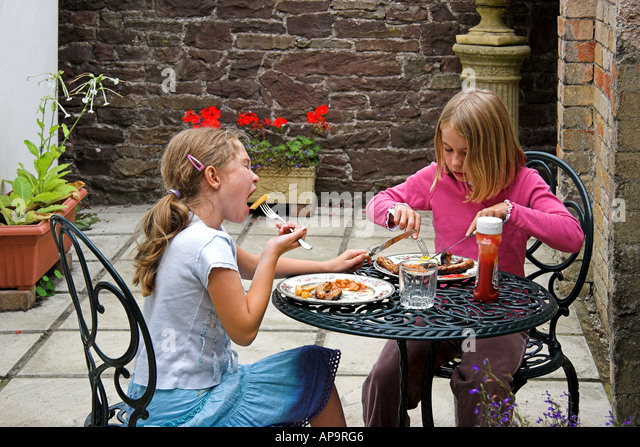 Young Girls Eating Lunch On Patio People Lifestyle Wales   Stock Image