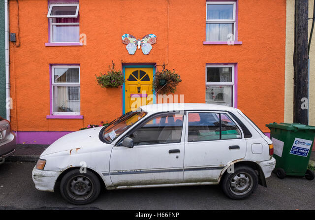 Old Toyota Starlet Car In Disrepair Parked Outside Colourfully Painted  Cottage In Kinsale, County Cork