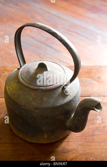 cast iron kettle over wooden table stock image