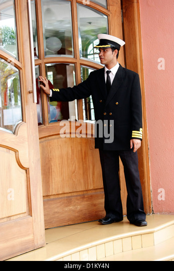 A doorkeeper opening the door for the guests to enter exit out of a building -