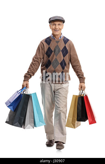 Full Length Portrait Of An Elderly Man Carrying Shopping Bags And Walking Towards The Camera Isolated