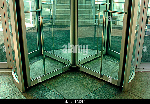 Revolving Glass Door Into A Modern Commercial Building   Stock Image