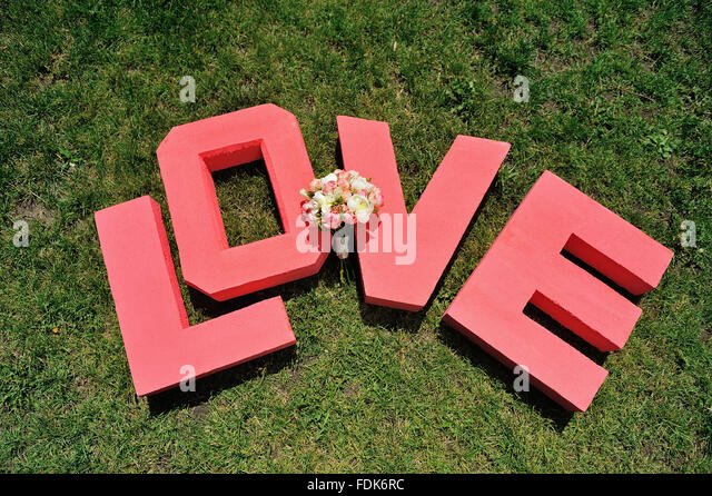 huge red letters wedding bouquet love and are located on green grass stock image