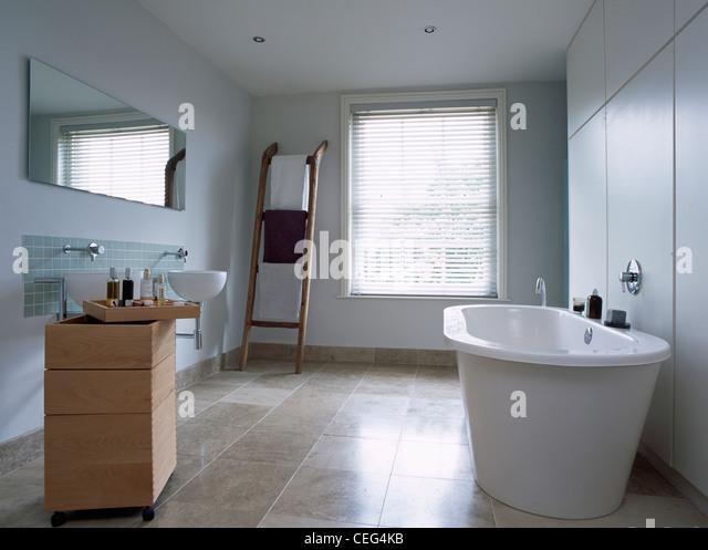 Freestanding bath and movable storage unit with basin in modern bathroom  with travertine floor and wooden. Floors Bathroom Bath Domestic Stock Photos   Floors Bathroom Bath
