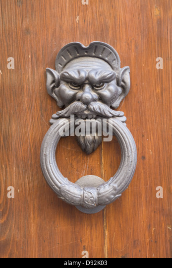 Metal,ornate Door Knocker On A Wooden Door In The Shape Of A Mans Face