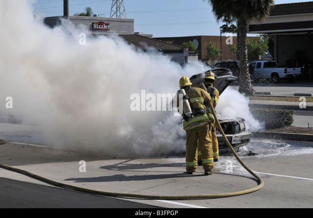 Charmant Firefighter Putting Out Fire On Burning Mercedes Stock Image