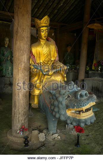 A gilded statue of a Taoist deity riding a dragon at the Huangge Temple in Husa. - Stock Image