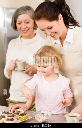 daughter and mother decorating cupcakes sprinkles stock image - Woman Decorating Cupcakes