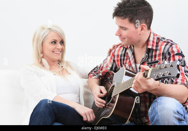 A Handsome Man Playing Guitar To Cute Girl