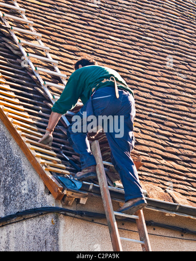 Awesome Workman Stepping Off Ladder Onto Roofing Ladder   France.   Stock Image