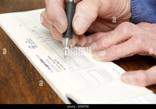 Bank cheque book stock photos bank cheque book stock images alamy elderly woman writing a cheque which is getting rarer these days co operative bank ccuart Images