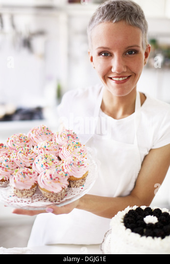portrait of woman holding hand made cupcakes stock image