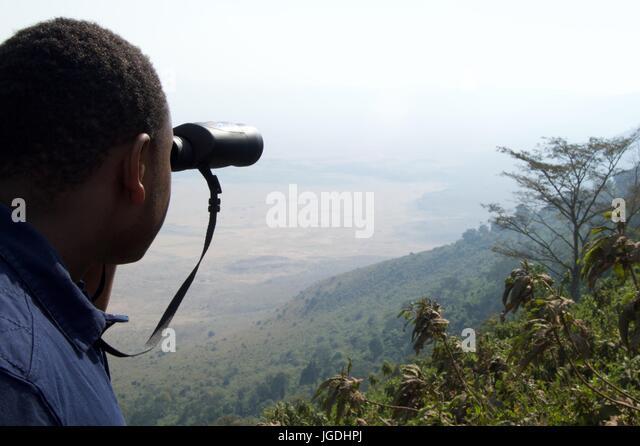 Man looks over crater rim with binoculars, Ngorongoro Crater, Tanzania - Stock Image